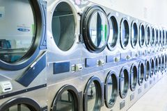 Laundromat. Industrial washing machines in a public laundromat stock image