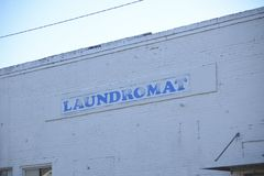 Laundromat and Clothes Washing Station. A Laundromat is a place that contain washing machines that wash and launder clothes using detergent, such as tide bleach stock images