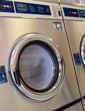 Laundromat washer running. A running high capacity washing machine at a laundromat. Long exposure, deep DOF, motion blur on the clothes in the wash royalty free stock image