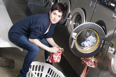 Laundry Day Woman Folds Infant Clothes Laundromat. A woman pulls clothes from the dryer at the laundromat royalty free stock photos