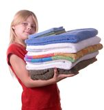 Laundry. Young girl helping with laundry carrying towels Stock Photography