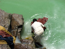 Laundry. A poor man from India, probably a lower class laundry ma, n washing his clothes on the banks of a contaminated green lake Royalty Free Stock Images