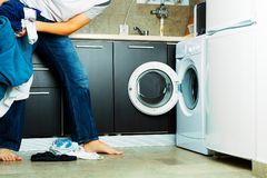 Laundry. Concept Man throwing his laundry into the washing machine Stock Photo