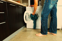 Laundry. Concept Man putting his laundry into the washing machine Royalty Free Stock Photography