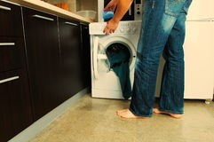 Laundry. Concept Man putting detergent into the washing machine Stock Photography