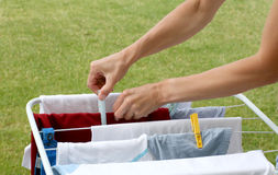 Laundry. Hanging on the clothesline, hands clipping  pegs Stock Photography