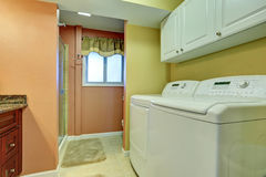 Laundry area in bathroom with white appliances. Stock Photos