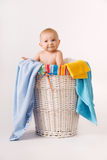 Laundry Basket Baby. A beautiful smiling baby sitting in a laundry basket of towels and blankets royalty free stock photo