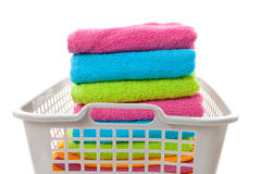 Laundry basket filled with colorful folded towels Stock Photos