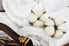 Fresh Laundered Towels Soap and Cotton Boll Flowers. Laundry basket filled white fluffy towels and cotton boll flowers. Focus on foreground with blurred royalty free stock images