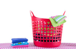 Laundry basket with folded wash. Red laundry basket with folded wash on an ironing board isolated over white Stock Photography