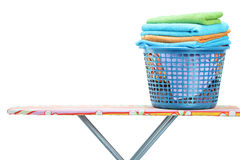 A laundry basket full of clothes on ironing board Royalty Free Stock Photo