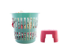 Laundry basket full of  clothes  and red plastic chair on white Royalty Free Stock Image