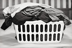 Laundry Basket. A monochrome photo of a laundry basket full of dirty bed linens sitting on a bed, waiting to be washed stock photo