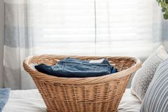 Laundry basket with neatly folded jeans. Wicker laundry basket with neatly folded jeans on the bed royalty free stock image