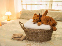 Laundry Basket with Teddy Bear. A basket of laundered towels with teddy bear on top, set in a bedroom Stock Images