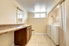 Laundry and bathroom interior in soft tones with tile floor. Royalty Free Stock Photography