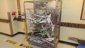 Laundry bin filled with clothes hangers parked in a restricted area. Metal cage laundry bin parked in restricted area dry stand pipe caution safety danger royalty free stock image