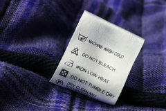 Laundry care label on scotch textile background Royalty Free Stock Photo