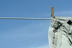 Laundry day. Pair of khaki pants hanging on the line with wooden clothespin Stock Image