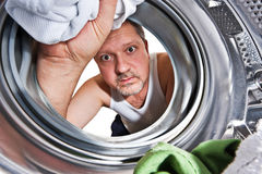 Laundry day. Man loading cloths to washing machine. View from inside the washing machine stock photos