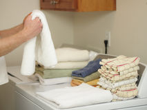 Laundry Day. Arms and hands of a male folding towels onto a dryer and washer in a laundry room Stock Photo