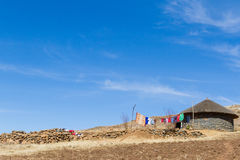 Laundry Day on the Mountaintop. An isolated Basotho hut basks in the sun on laundry day in rural Lesotho village during the dry winter season stock image
