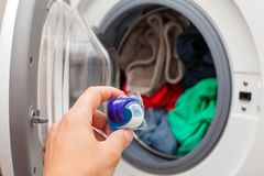 Laundry detergent pod. Close up picture of person holding laundry detergent 3 in 1 pod capsule, washing machine with laundry in the background stock photos