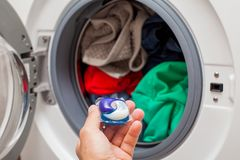 Laundry detergent pod. Close up picture of person holding laundry detergent 3 in 1 pod capsule, washing machine with laundry in the background royalty free stock photography