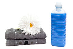 Laundry detergent with towels and flower Royalty Free Stock Image