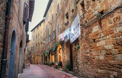 Laundry dried on a rope outside a brick house on narrow street of town of Tuscany royalty free stock images