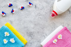 Laundry. Dry and liquid detergents near clean towel on grey stone background top view copyspace Royalty Free Stock Photography