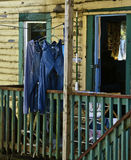 Laundry Hanging to Dry. Blue jeans and grey sweat pants, laundry hung out to dry on the porch of an old tattered yellow and turquoise wooden building in Stock Images