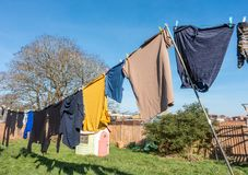 Laundry drying on a washing line. In a back garden on a sunny winter`s day royalty free stock image