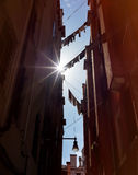 Laundry hanging on clothesline. Laundry clothes hanging on clothesline between the houses of old streets Stock Images