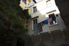 Laundry hanging in an Italian courtyard in the hot summer light. Stock Image