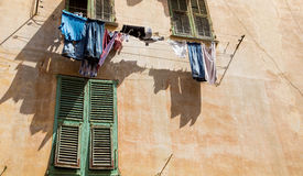 Laundry Hanging Over Stucco Wall and Green Shutter Stock Images