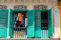 Laundry hanging seen through open wood shutter windows Singapore Royalty Free Stock Photos