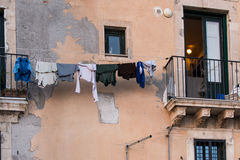 Laundry hanging to dry on a wire in front of a wall very spoiled. Laundry hanging to dry on a wire with the clothespins against the badly damaged facade of a Stock Photo