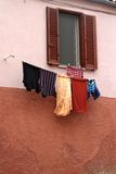 Laundry hanging from a window Stock Images