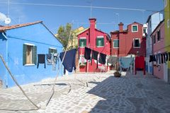 Laundry hangs across the colorful streets of Burano - Venice Stock Images