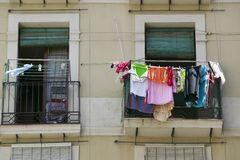 Laundry hangs in window of old section of Barcelona, Spain Stock Photos