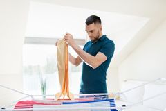 Man taking laundry from drying rack at home Royalty Free Stock Photography