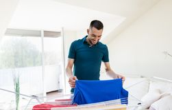 Smiling man with laundry and drying rack at home Stock Image