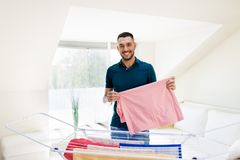 Smiling man with laundry and drying rack at home Royalty Free Stock Photo