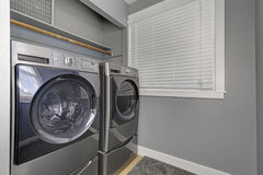 Laundry interior with gray walls, carpet and modern appliances. Royalty Free Stock Images