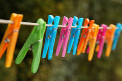 Laundry line. Colorful clothes pegs hanging on a laundry line royalty free stock image
