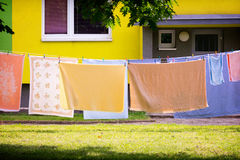 Laundry on line. Colorful laundry, sheets and towels, hanging on line in front of residential house royalty free stock photo