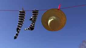 Laundry line with woman socks and summer straw hat in wind on blue sky stock footage
