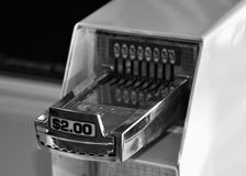 Laundry Machine Coin Receiver. A metal laundromat coin receiver demanding eight quarters for service Stock Image